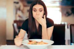 Kvinna som känner sig sjuk, medan äta dålig mat i en restaurang Royaltyfri Fotografi