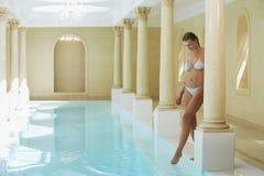 Kvinna som känner vattentemperaturen vid poolsiden Fotografering för Bildbyråer