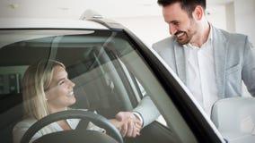 Kvinna som köper en bil i återförsäljaresammanträde i hennes nya automatisk royaltyfri foto