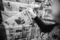 Kvinna som köper internationell press med Emmanuel Macron och flottan Arkivfoto