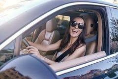 Kvinna som kör bilen med det öppnade fönstret arkivbild