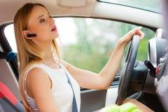 Kvinna som kör bilen med hörlurar med mikrofon Royaltyfria Bilder