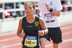 Kvinna som kör den sista elasticiteten på Stockholm Stadion i ASICS-St Royaltyfria Foton
