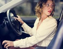 Kvinna som kör en bil i omvänt royaltyfri fotografi