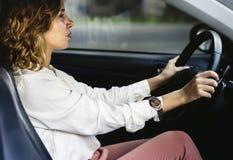 Kvinna som kör en bil på en väg arkivbilder