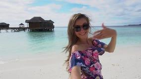 Kvinna som kör till havet på stranden i Maldiverna och inviterar hennes vän att sammanfoga arkivfilmer