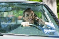 Kvinna som kallar mobiltelefonen under körning av en bil Arkivbild