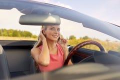 Kvinna som kallar på smartphonen på den konvertibla bilen royaltyfri fotografi