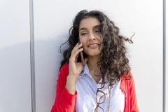 Kvinna som kallar på telefonen som går i gatan Royaltyfria Bilder