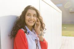 Kvinna som kallar på telefonen som går i gatan Arkivbild