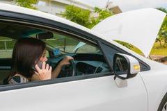 Kvinna som kallar räddningstjänst med hennes brutna bil royaltyfri bild
