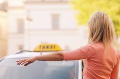 Kvinna som kallar taxien Arkivbilder