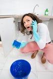 Kvinna som kallar till rörmokaren Through Mobile Phone Royaltyfri Foto