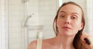 Kvinna som kammar hår som ser kameran och att le lager videofilmer