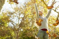 Kvinna som kastar Autumn Leaves In The Air Arkivbilder