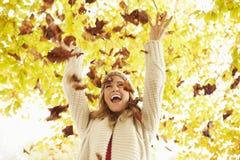 Kvinna som kastar Autumn Leaves Into The Air royaltyfri bild