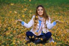 Kvinna som kastar Autumn Leaves Into The Air Arkivfoton