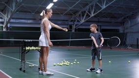 Kvinna som kastar bollen, medan övning slogg med pysen på tennisbanan arkivfilmer