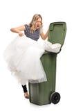 Kvinna som kastar hennes bröllopsklänning i avfall Royaltyfri Bild