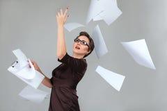 Kvinna som kastar papperssidor royaltyfri foto