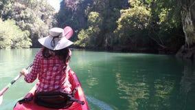 Kvinna som kayaking i bakre punkt för härlig baksida för lagunhandlingkamera av sikten av flickan som paddlar på kajakfartyget stock video
