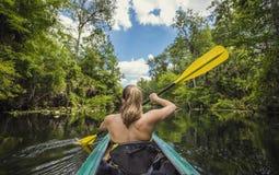 Kvinna som Kayaking ner en härlig tropisk djungelflod arkivfoton