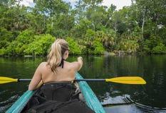 Kvinna som Kayaking ner en härlig tropisk djungelflod royaltyfri foto