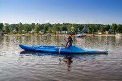 Kvinna som kayaking på en lugna sjö Arkivfoton