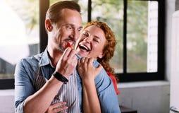 Kvinna som kelar hans make och skratta Royaltyfri Fotografi