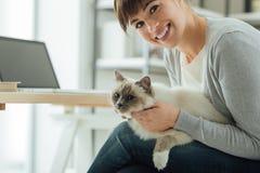 Kvinna som kelar hennes älskvärda katt arkivbilder