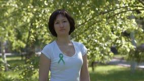 Kvinna som klämmer fast det gröna medvetenhetbandet stock video