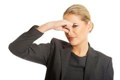 Kvinna som klämmer näsan på grund av äcklig lukt royaltyfri fotografi