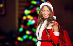 Kvinna som kläs för jul som rymmer shoppingpåsar Royaltyfria Foton