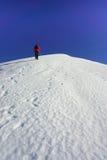 Kvinna som klättrar en snölutning arkivfoto