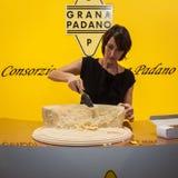 Kvinna som klipper Grana Padano ost in i stycken på Golosaria 2013 i Milan, Italien Royaltyfri Bild
