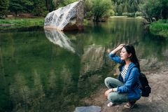 Kvinna som knäfaller ner att koppla av på spegelsjön arkivbilder