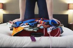 Kvinna som knäfaller på den Overstuffed resväskan Fotografering för Bildbyråer