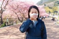 Kvinna som känner sig opasslig med pollenallergi under det sakura trädet Arkivbilder