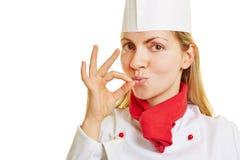 Kvinna som kockkocken som ger tecknet av bra smak Arkivfoto
