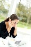 Kvinna som koncentrerar, medan läsa på hennes bärbar dator arkivfoto