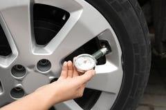 Kvinna som kontrollerar bilgummihjultryck med luftmåttet fotografering för bildbyråer