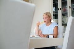 Kvinna som kontrollerar bills och gör budgeten Royaltyfri Fotografi