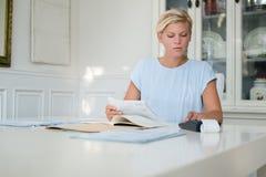 Kvinna som kontrollerar bills och gör budgeten Royaltyfri Bild