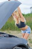 Kvinna som kontrollerar bilmotorn Arkivbild