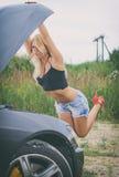 Kvinna som kontrollerar bilmotorn Arkivbilder