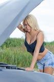 Kvinna som kontrollerar bilmotorn Fotografering för Bildbyråer