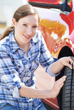 Kvinna som kontrollerar däckmönster på bildäcket med måttet arkivfoto