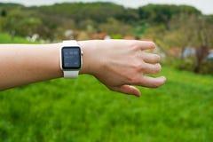 Kvinna som kontrollerar hennes Apple klocka i gräsplanen Arkivbild