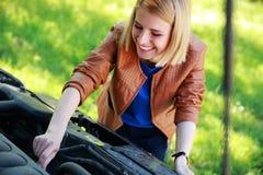 Kvinna som kontrollerar hennes bilmotor Royaltyfri Foto