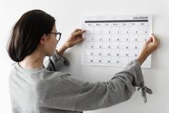 Kvinna som kontrollerar kalendern på väggen royaltyfri bild